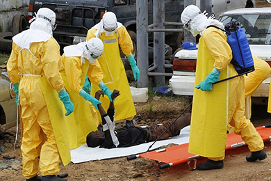 EPA // Liberian health workers on an Ebola burial team collecting the body of a victim of the disease on the outskirts of Monrovia.