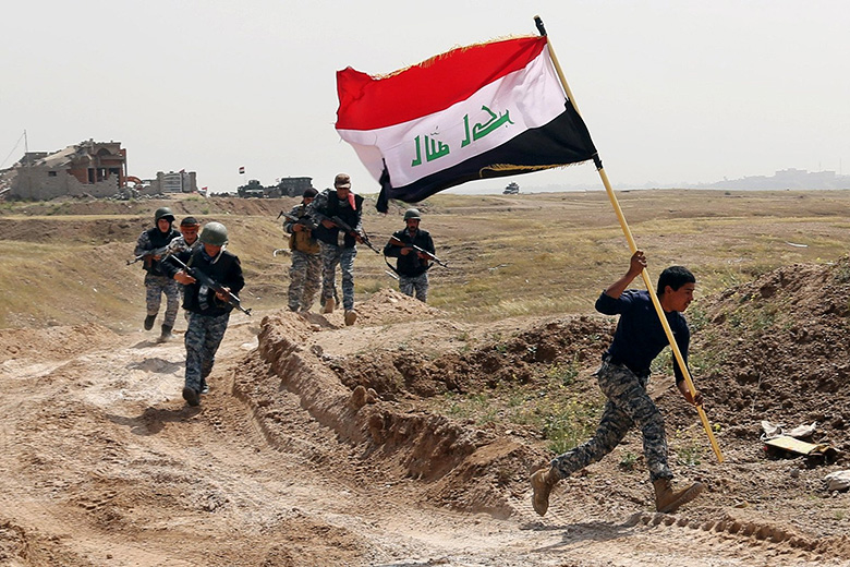 Khalid Mohammed/AP // A member of the Iraqi security forces runs to plant the national flag as they surround Tikrit during clashes to regain the city from Islamic State militants.