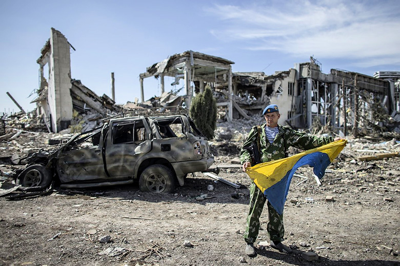 Marko Djurica/Reuters // A pro-Russian rebel with a captured Ukrainian flag at the destroyed airport in Luhansk, eastern Ukraine, on September 14.
