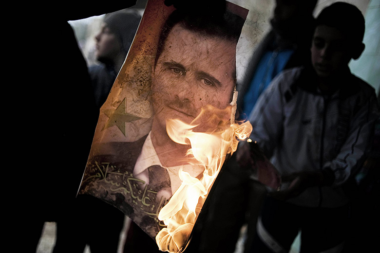 Alessio Romenzi/AFP/Getty Images // A member of the Free Syrian Army holds a burning portrait of embattled President Bashar al-Assad in Al-Qsair, 25kms southwest of the flashpoint city Homs.