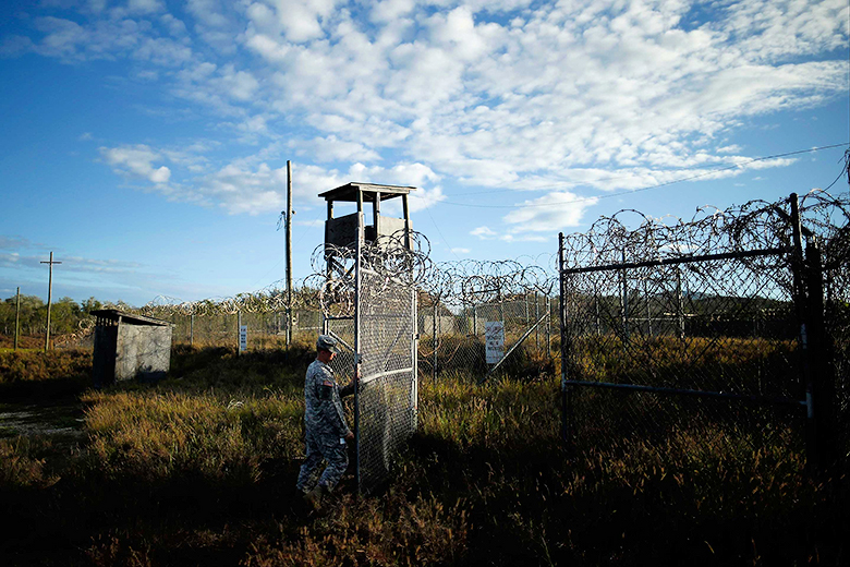 Charles Dharapak/AP // A U.S. soldier closes the gate at a now-abandoned detention facility at Naval Station Guantanamo Bay, Cuba, Nov. 13, 2013.