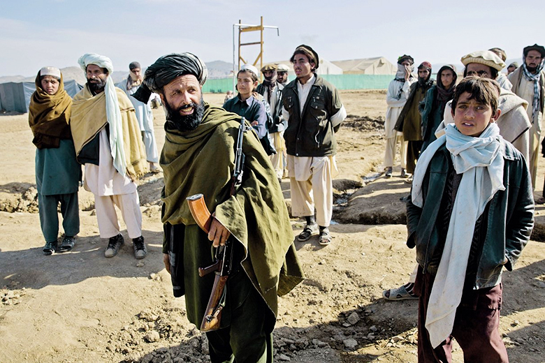 AP Photo/Massoud Hossaini // An armed Afghan security officer mingles with Pakistani refugees at Gulan camp in Khost province, Afghanistan, on 19 January 2015.