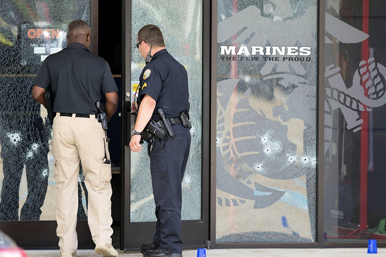 John Bazemore/AP  // Police officers enter the Armed Forces Career Center through a door riddled with bullet holes after a gunman opened fire on the building in Chattanooga, Tenn.