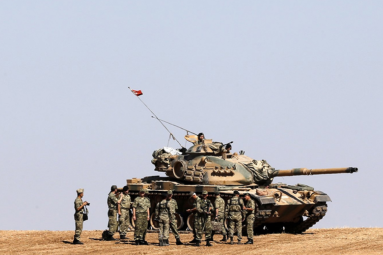 Reuters/Umit Bektas // Turkish Land Forces Commander General Hulusi Aker and other officers gather around an army tank on the Turkish-Syrian border near the southeastern town of Suruc in Sanliurfa province October 6, 2014.