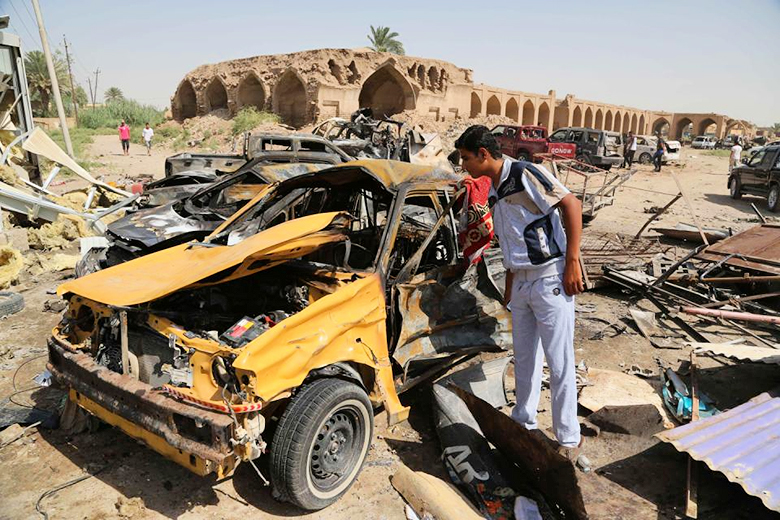 AP Photo/Karim Kadim // Civilians inspect the aftermath of a suicide car bombing at a busy market in Khan Bani Saad in the Diyala province, about 20 miles (30 kilometers) northeast of Baghdad, Iraq, Saturday, July 18, 2015.