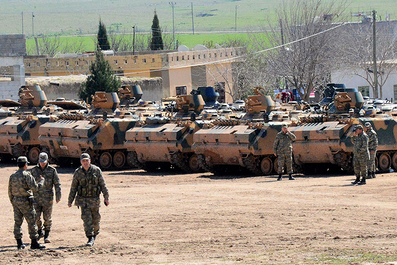 Ilyas Akengin/AFP Photo // Turkish army vehicles and personnel wait at an assembly area in Suruc, near the Syrian border, Feb. 23, 2015.