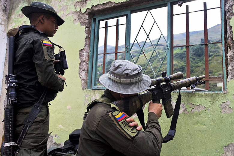 Luis Robayo/AFP/Getty Images // Colombian police at a house destroyed by the Revolutionary Armed Forces of Colombia in El Mango, Colombia.