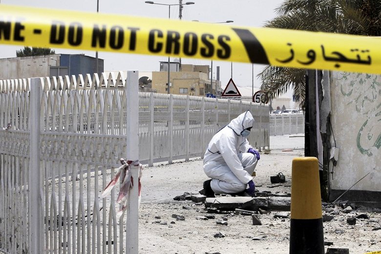 Mohammed Al-Shaikh/AFP Photo // A Bahraini forensic police officer inspects the site of a bomb blast in the village of Sitra, south of Manama, July 28, 2015.