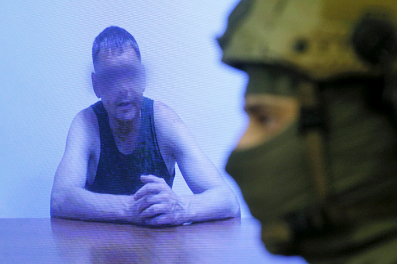 Reuters/Valentyn Ogirenko // An officer of the Security Service of Ukraine (SBU) stands next to a monitor showing a man, who according to SBU is a Russian army major detained by Ukrainian servicemen at the weekend, during a news briefing in Kiev, Ukraine, July 29, 2015.