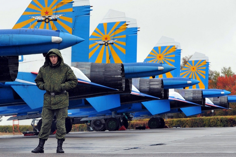 Vyacheslav Oseledko/AFP/Getty Images // A Russian officer and Su-27 fighter jets at the Russian air force base in Kant, Kyrgyzstan, in 2013.