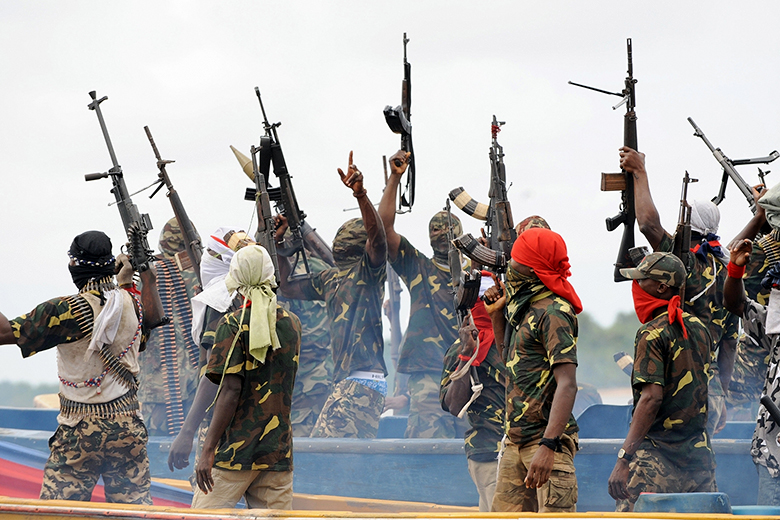Pius Utomi Ekpei/AFP/Getty Images // Fighters with the Movement for the Emancipation of the Niger Delta (MEND) raise their rifles to celebrate news of a successful operation in 2008.