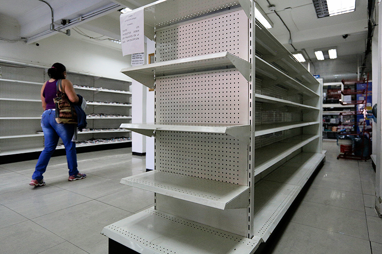 Reuters/Marco Bello // A woman walks past empty shelves at a drugstore in Caracas, Venezuela.