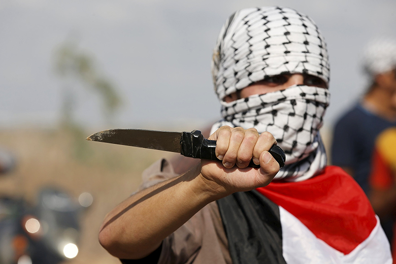 Reuters/Mohammed Salem // A masked Palestinian protester holds a knife during a protest near the Israeli border fence in northeast Gaza October 9, 2015.