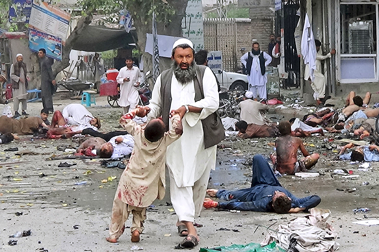 Reuters // A man leads an injured boy by the hands after the suicide attack in Jalalabad, Afghanistan.